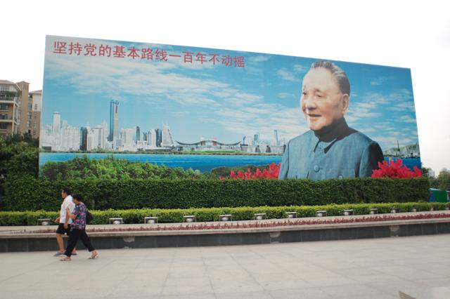 交差点の脇に大々的に設置された看板。鄧小平の「党の基本路線を堅持すれば、100年は揺るがない」という言葉が書かれている